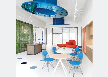 The blue reflective circular discs ... framing vignettes of the open-plan space.