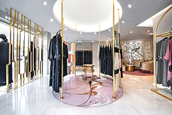 Gold is used on custom undulating curved fixtures from which clothing is displayed.