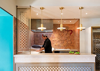 An open modern design tandoor kitchen allows guests to see chefs preparing traditional bread.