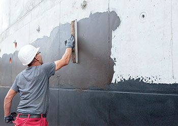 The bituminous compound reinforces the barrier effect against water pressure on a concrete wall.