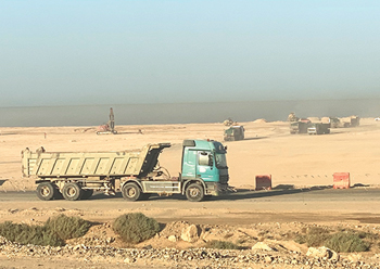 Scores of trucks move up and down on the road linking Sharma, Al Muweileh and Duba.