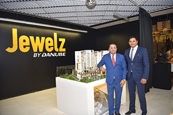 Sajan and Rahman pose in front  of a model of Jewelz.