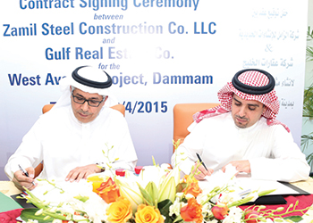 Al Zamil (right) and Albadah sign the agreement.