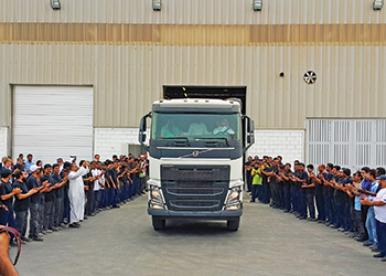 Employees cheer as the first Volvo truck rolls out of the KAEC plant assembly line.