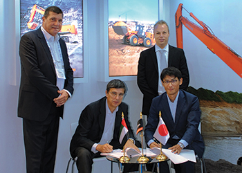 Officials of Hitachi Construction Equipment and MECET sign the agreement.