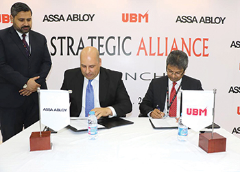 UBM and Assa Abloy officials sign the agreement.